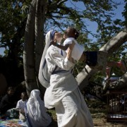 Missionaries of Charity holds up a Haitian girl in Port-au-Prince, Haiti, Tuesday Dec. 21, 2010, scheduled to be transported to France along with 317 other Haitian children for Christmas 2010 (AP Photo/Ramon Espinosa).