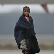A Haitian child walks to a bus after arriving at a military airport in Eindhoven, Netherlands, along with 105 other children from Haiti, aged 6 months to 7 years, on Thursday Jan. 21, 2010, (AP/Peter Dejong).