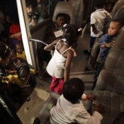 Children board a bus headed for the airport in Port-au-Prince. Several children are being sent for adoption to France by the school Lycee Francais and the French Embassy in Haiti (AP Photo/Julie Jacobson).