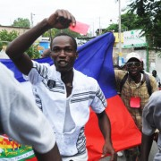 "Protester brandishing a red card to say ""You're out!"" to the Martelly-Lamothe regime (Photo: Radio Kiskeya)."